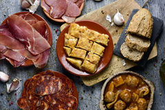 Assortment of spanish cold meats and tapas. High-angle shot of some plates with an assortment of different spanish cold meats, such as serrano ham, chorizo or Stock Photography