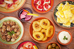 Assortment of Spanish tapas and sangria on a rustic table Stock Images