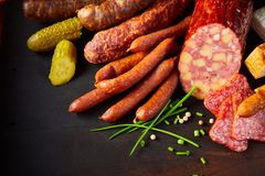 Assortment of speciality seasoned spicy sausages. Arranged in the corner on a dark background with chives, peppercorns, pickled cucumbers or gherkins and copy royalty free stock image