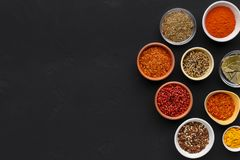 Assortment of spices in bowls on black background stock images