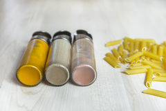 Assortment of spices glass bottles and pasta on wooden table Stock Photography