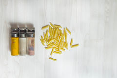 Assortment of spices glass bottles and pasta on wooden table Stock Images