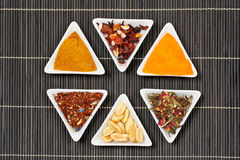 Assortment of spices over a bamboo mat Stock Photo