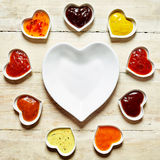 Assortment of spicy dips and marinade sauces. Presented in a small heart shaped bowls around an empty large heart-shaped bowl on a wooden background, overhead stock photo