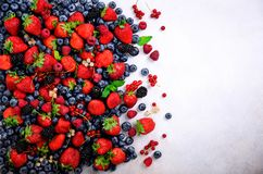 Assortment of strawberry, blueberry, currant, mint leaves. Summer berries background with copy space for your text. Top royalty free stock images