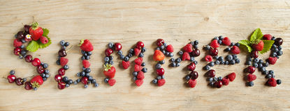 Assortment of summer fresh berries forming the word. On wooden background Stock Photos