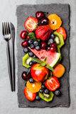 Assortment summer fresh berries and fruits on black slate plate Stock Images