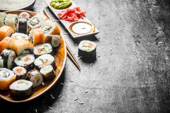 Assortment of sushi rolls with salmon and vegetables on a plate. On dark rustic background stock image