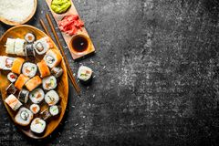Assortment of sushi rolls with salmon and vegetables on a plate. On dark rustic background royalty free stock images