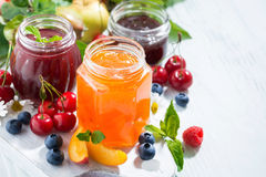 Assortment of sweet jams and seasonal fruits on white background. Closeup royalty free stock photography