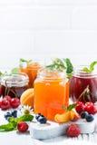 Assortment of sweet jams and seasonal fruits on white background Stock Photo