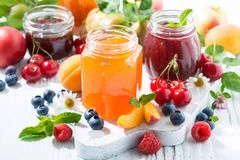 Assortment of sweet jams and seasonal fruits on white table Stock Images