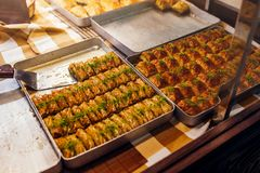 Assortment of Turkish baklava with pistachio on cafe showcase. Sweet baklawa on tray in store. Arabic dessert. Turkish cuisine Stock Photos
