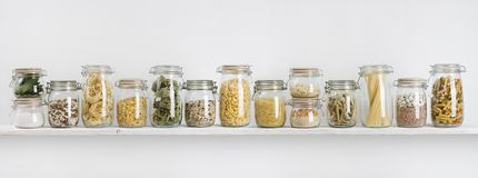 Assortment of uncooked groceries in glass jars arranged on shelf.  stock image