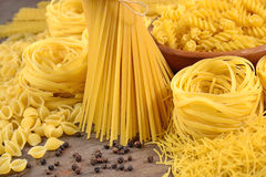 Assortment of uncooked Italian pasta and black pepper on a woode Royalty Free Stock Photos