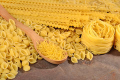 Assortment of uncooked Italian pasta on a wooden background Royalty Free Stock Photo