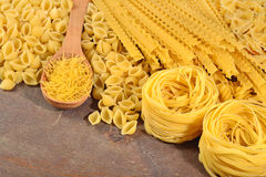 Assortment of uncooked Italian pasta on a wooden background Royalty Free Stock Images