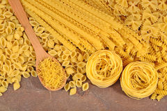 Assortment of uncooked Italian pasta on a wooden background Stock Photography