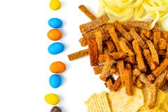 Assortment of Unhealthy Snacks: chips, onion rings, crackers top view, flat lay. Unhealthy eating concept royalty free stock photography