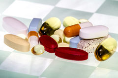 An Assortment of Various Medicines And/Or Vitamin Supplements. On a Checkered Background Stock Photography