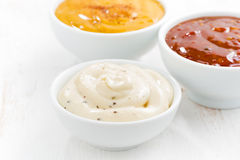 Assortment various sauces in bowls on white table Royalty Free Stock Photos