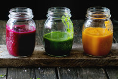 Assortment of vegetable smoothies. From carrot, beetroot and spinach in glass jars. Over old wooden table. Dark rustic style, natural day light stock photography