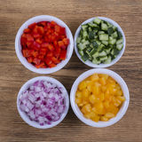 Assortment of vegetables sliced. Peppers, tomatoes, cucumber and onion in bowls Royalty Free Stock Photography