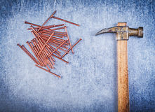 Assortment of vintage claw hammer copper construction nails on m Royalty Free Stock Photos