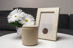 An assortment of a white artificial flower, cement candle and a gray picture frame