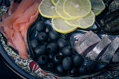 Assorty des poissons, olives, tranches de citron sur le plat oriental toned Photographie stock