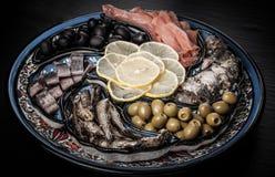 Assorty des poissons, olives, tranches de citron sur le plat oriental toned Photo stock