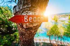 Assos-Dorf im Morgensonnen-Strahlnlicht, Kefalonia Griechenland Setzen Sie hölzernes Pfeilzeichen auf einer Kiefer auf den Strand lizenzfreie stockfotos