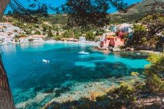 Assos-Dorf, Kefalonia, Griechenland Ansicht über tourquise transparentes Wasser, das zwischen grüner Kiefernwaldung gestaltet wir lizenzfreies stockbild