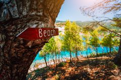 Assos village Kefalonia. Greece. Beach wooden arrow sign on a pine tree showing direction to small hidden beach.  royalty free stock photo