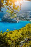 Assos village, Kefalonia. Greece. White yacht in blue bay framed by nature. Turquoise colored bay in Mediterranean sea. Surrounded by pine trees under bright royalty free stock image