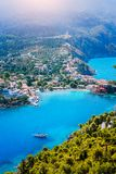 Assos village in morning light, Kefalonia. Greece. White lonely yacht in beautiful turquoise colored bay lagoon water. Surrounded by pine and cypress trees royalty free stock images