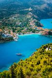 Assos village in morning light, Kefalonia. Greece. White lonely yacht in beautiful turquoise colored bay lagoon water. Surrounded by pine and cypress trees royalty free stock photography