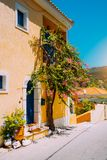 Assos village. Traditional yellow colored greek house with bright blue door and windows. Fucsia plant flowers around royalty free stock photography