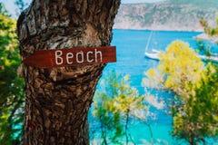 Assosdorp, Kefalonia Griekenland Teken van de strand het houten pijl op een pijnboomboom die richting tonen aan klein verborgen s stock afbeeldingen
