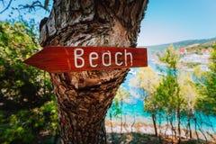Assosdorp in ochtendlicht, Kefalonia Griekenland Teken van de strand het houten pijl op een pijnboomboom die richting tonen aan k royalty-vrije stock fotografie