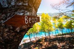 Assosdorp in ochtendlicht, Kefalonia Griekenland Teken van de strand het houten pijl op een pijnboomboom die richting tonen aan k stock foto's