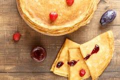 Assottigli i pancake caldi con le bacche sulla tavola Fotografia Stock
