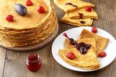 Assottigli i pancake caldi con le bacche sulla tavola Immagini Stock