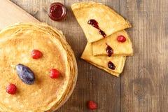 Assottigli i pancake caldi con le bacche sulla tavola Fotografie Stock