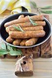 Assottigli le salsiccie fritte in una pentola su un fondo di legno Immagine Stock