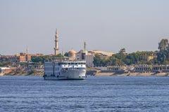 12 11 2018 Assuan, Ägypten, eine enorme Kreuzfahrtfähre, die entlang einen Nil vor dem hintergrund einer Stadt sich bewegt stockfoto