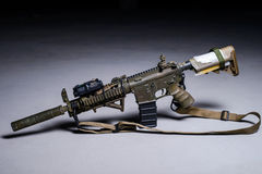 Assult automatic rifle with silencer. Painted assult automatic rifle with silencer and laser sight royalty free stock photo