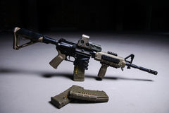 Assult rifle and magazines with bullets. Assult automatic rifle with collimator sight and magazines with bullets royalty free stock photo