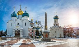 The main temples of the Sergius Lavra. The Assumption Cathedral, a well, a chapel, an obelisk and the Dukhov Church in the Sergius Lavra on a sunny winter day Stock Photos