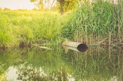 Assunto da ecologia: o esgoto derrama desperdiça para fora ao lago/água de esgoto do esgoto polui um lago imagens de stock royalty free